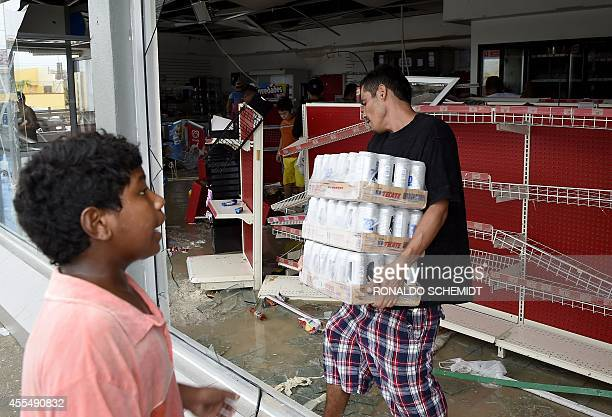 People loot a supermarket in Cabo San Lucas on September 15 2014 after hurricane Odile knocked down trees and power lines in Mexico's Baja California...