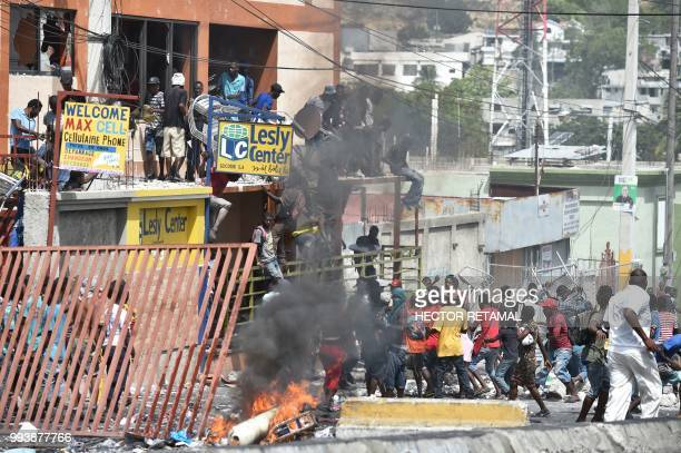 People loot shops in Delmas a commune near PortauPrince during protests against the rising price of fuel on July 8 2018 Fresh looting broke out on...