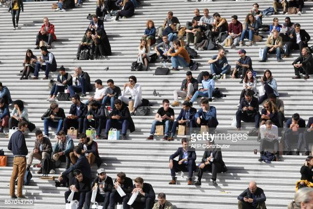 People mainly employees sit during their lunch break on the stairs of the Big Arche building in the La Defense business district in Courbevoie on...