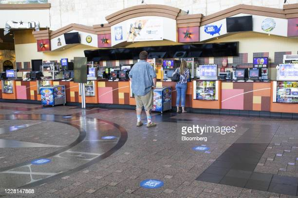 People maintain social distancing as they wait in line for a concessions counter at a Regal Cinemas theater in Austin, Texas, U.S., on Friday, Aug....