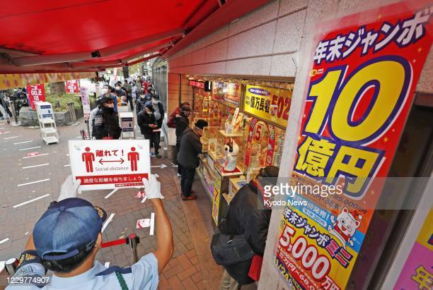 People maintain social distancing when lining up in front of a lottery booth in Tokyo's Ginza district on Nov. 24 as sales of year-end lottery...