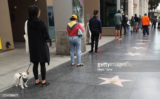 People maintain social distancing while standing in line to enter a Trader Joe's, along the Hollywood Walk of Fame, as the coronavirus pandemic...