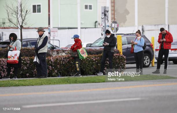 People maintain social distancing while standing in line to enter a Trader Joe's as the coronavirus pandemic continues on March 25 2020 in Los...
