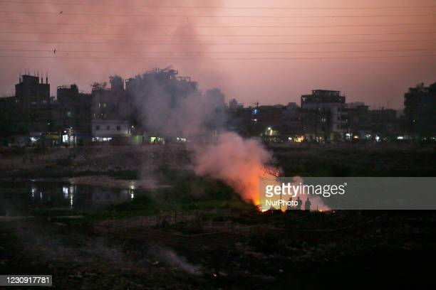 People make a fire on a pile of polythene as it creates toxic smoke beside the old Buriganga River Channel at keraniganj in Dhaka, Bangladesh on...
