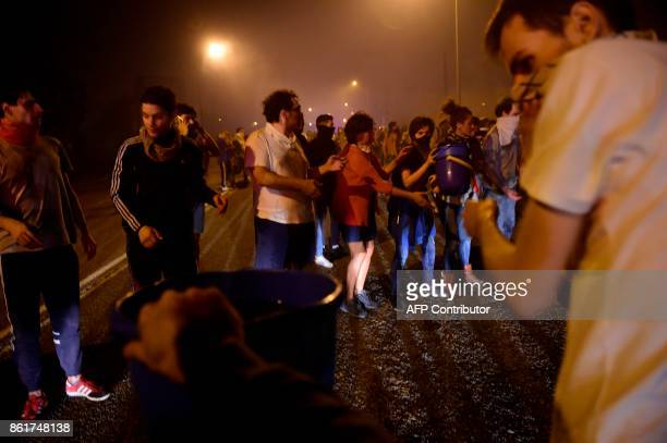 People make a queue to carry buckets with water to extinguish wildfires in Vigo northwestern Spain on October 15 2017 Hundreds of firefighters...