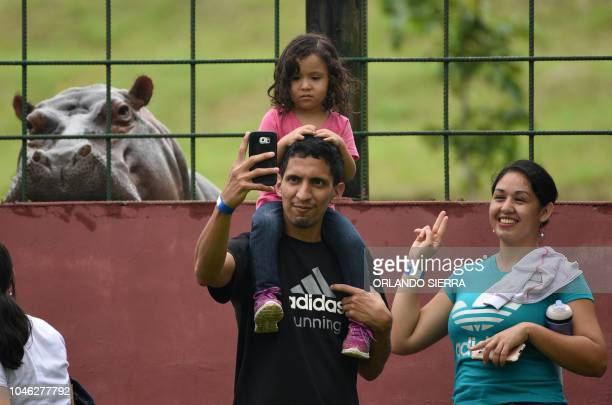 People make a selfie with a hippo at the Joya Grande zoo and ecopark in Santa Cruz de Yojoa Cortes department 160 km north of Tegucigalpa Honduras on...