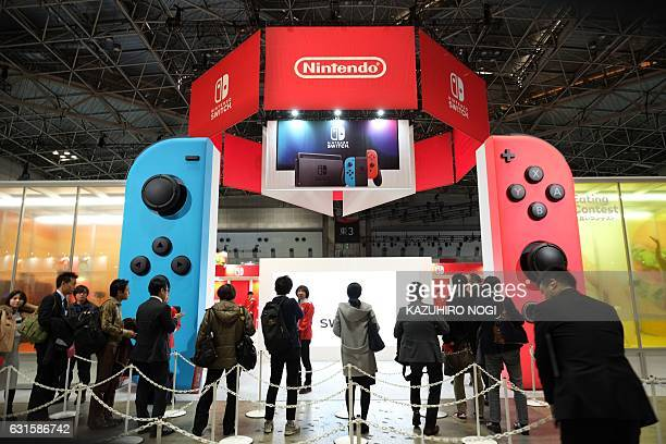 People make line up for Nintendo's new video game console Switch during its presentation in Tokyo on January 13 2017 Nintendo on January 13 unveiled...
