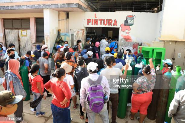 People make long queues to refill oxygen tanks for their relatives who are under treatment against COVID on May 09, 2020 in Iquitos, Peru. Iquitos,...
