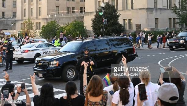 People make rude gestures towards President Donald Trump's motorcade as he returns to the White House after playing golf in Washington, DC on...