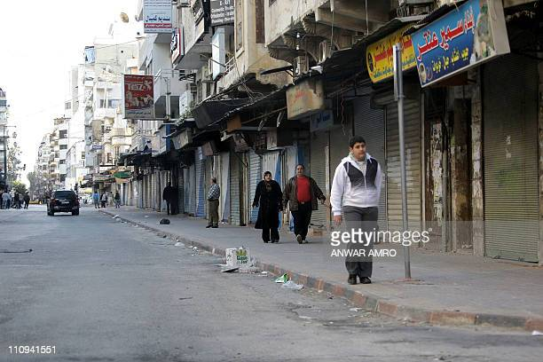 People make their along a mostly deserted street past shutterd shops in the Northern city of Latakia some 350 km northwest Damascus on March 27 2011...