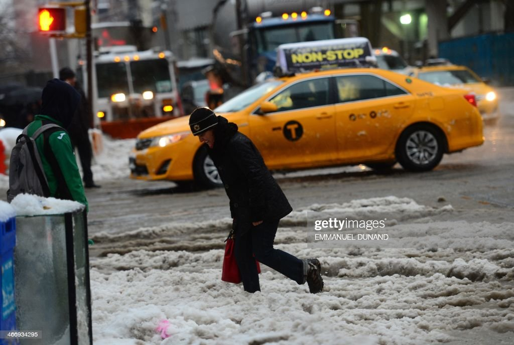 People make their way across a street after an overnight snow storm followed by freezing rain in New York, February 5, 2014. AFP PHOTO/Emmanuel Dunand