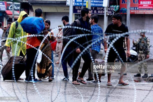TOPSHOT People make their way along a street in Jammu on August 5 2019 Authorities in Indianadministered Kashmir placed large parts of the disputed...
