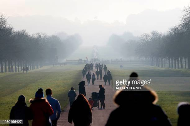 People make their way along The Long Walk toward the Copper Horse Statue of King George III as they exercise in Windsor, west of London, on January...