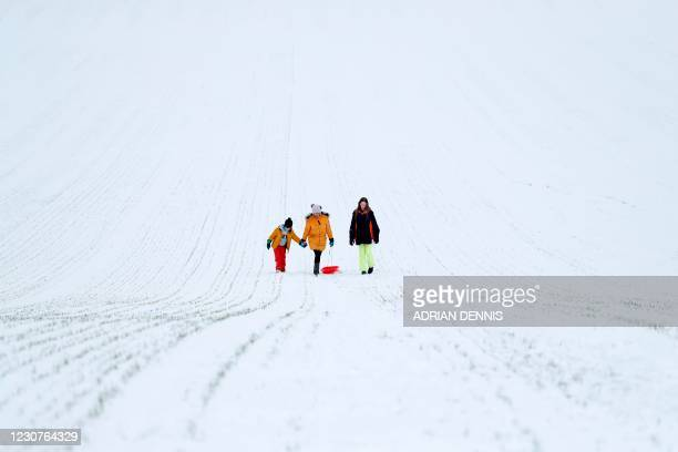 People make their way back up the hill after riding a sled down a snow-covered field beside St. Mary's Church after heavy snowfall in Hartley...