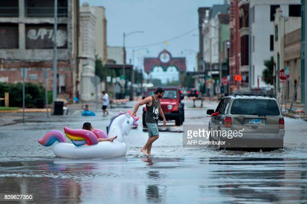 TOPSHOT People make their way down partially flooded roads following the passage of Hurricane Harvey on August 26 2017 in Galveston Texas / AFP PHOTO...