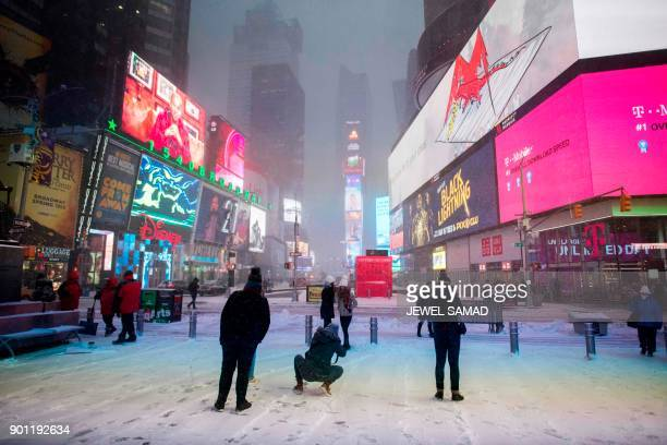 TOPSHOT People make their way in Times Square during a winter storm in New York on January 4 2018 The US National Weather Service warned that a major...