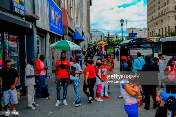People make their way on a local street in downtown Newark New Jersey on June 7 a half century after the 1967 riots / AFP PHOTO / EDUARDO MUNOZ...