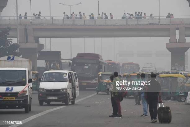 People make their way on a street in smoggy conditions in New Delhi on November 4 2019 Millions of people in India's capital started the week on...