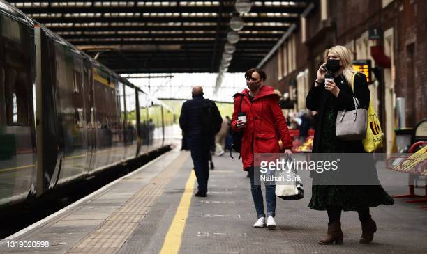 People make their way onto a London Northwestern Railway Train at Stoke-on-Trent Train Station on May 20, 2021 in Stoke, England. The British...