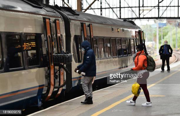 People make their way onto a train at Stoke-on-Trent Train Station on May 20, 2021 in Stoke, England. The British government has created a...