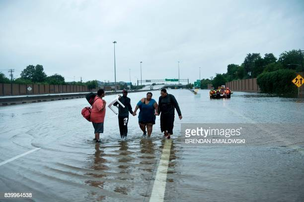 People make their way onto an I610 overpass after being rescued from flooded homes during the aftermath of Hurricane Harvey August 27 2017 in Houston...