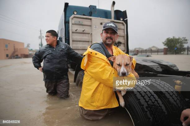 People make their way out of a flooded neighborhood after it was inundated with rain water, remnants of Hurricane Harvey, on August 28, 2017 in...