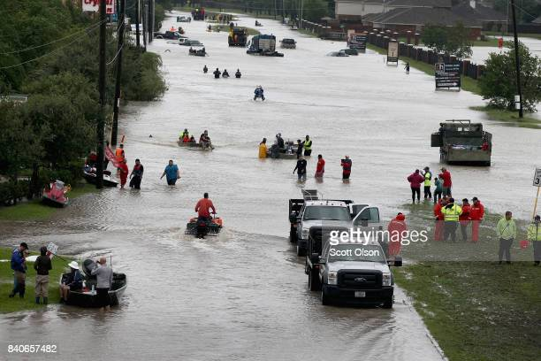 People make their way out of a flooded neighborhood after it was inundated with rain water following Hurricane Harvey on August 29, 2017 in Houston,...