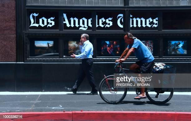People make their way past the Los Angeles Times office building in downtown Los Angeles California on July 16 2018 The newspaper is preparing a...