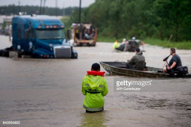 People make their way through a flooded street during the aftermath of Hurricane Harvey on August 29, 2017 in Houston, Texas. Floodwaters have...