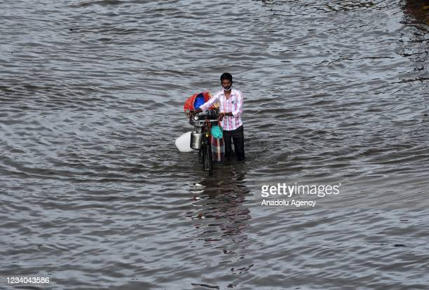 People make their way through a waterlogged street after heavy rainfall in Mumbai, India on July 18, 2021.