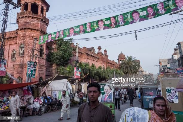 People make their way through an intersection as banners of Nawaz Sharif and Shahbaz Sharif both leaders of political party Pakistan Muslim LeagueN...