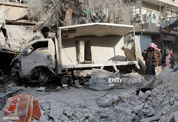 People make their way through the debris following a reported Syrian government forces air strike the day before in the northern city of Aleppo on...