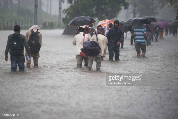 People make their way through the waterlogged road as it rains very heavily near Tilak Nagar railway station on July 9 2018 in Mumbai India Indias...