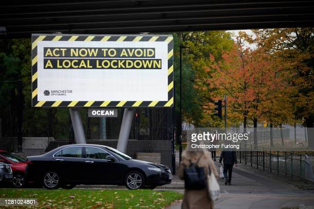 People make their way to work past an electronic covid warning sign advises people entering Manchester city centre on October 19, 2020 in Manchester,...