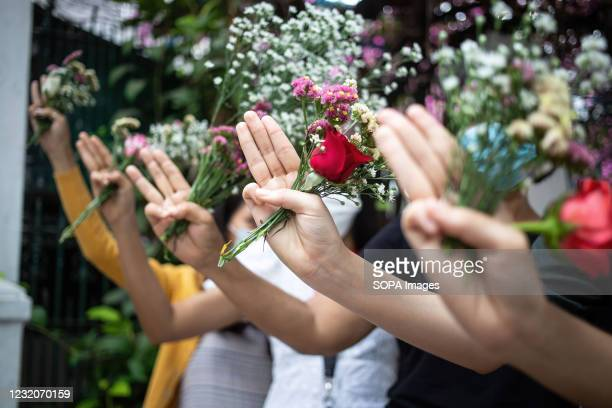 People make three-finger salutes while holding flowers in memory of the victims of the violent protests against the February 1 military takeover....