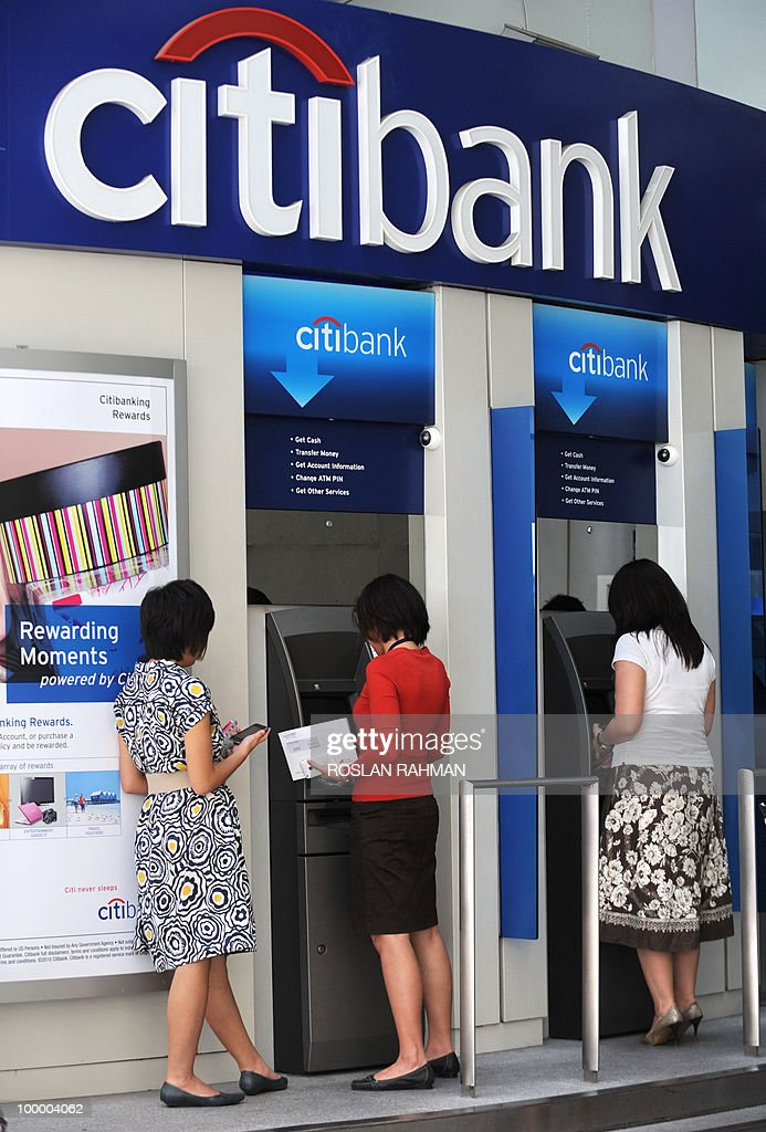People make transactions through Citibank automated teller machines (ATMs) in Singapore on May 20, 2010. The euro fell against other major currencies in Asia after a short-lived rally on intervention rumours amid persistent concerns over eurozone debts, analysts said.