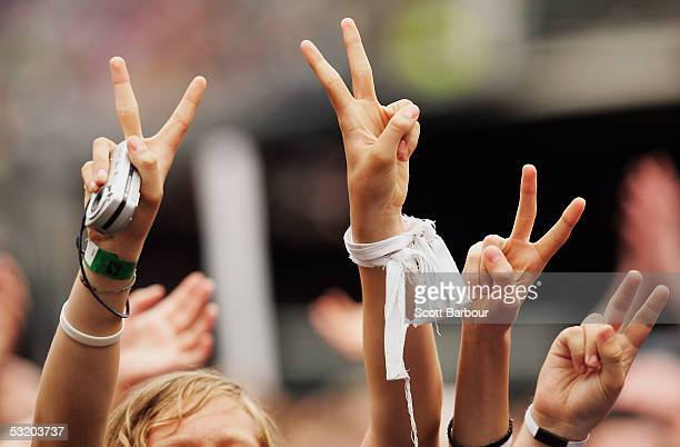 People make 'victory' signs in the crowd at the Live 8 Edinburgh concert at Murrayfield Stadium on July 6 2005 in Edinburgh Scotland The free gig...