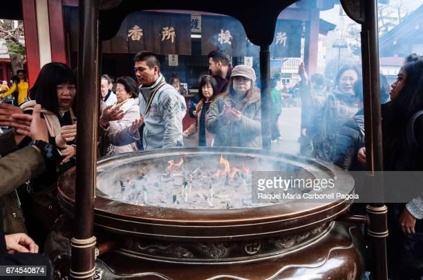 People making offerings around big incense burner in Sensoji temple