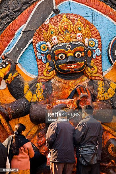 people making offerings at a deity wall - merten snijders stock pictures, royalty-free photos & images
