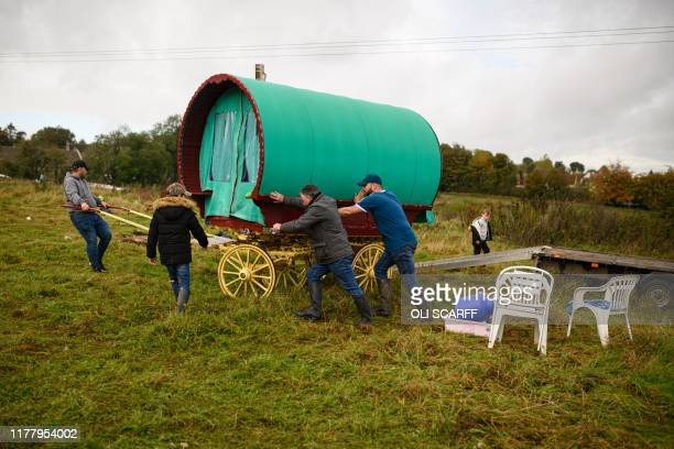 People manoeuvre a traditional caravan onto a trailer at the biannual Stow Horse Fair in the town of StowontheWold England on October 24 2019 The...