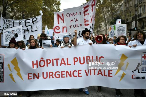 People march behind a banner reading in French Public hospital in lifethreatening emergency during a demonstration on November 14 2019 in Paris as...
