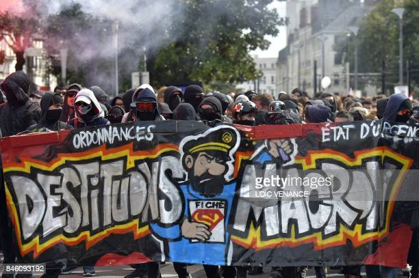 People march behind a banner reading 'Let's depose Macron' during a protest called by several French unions against the labour law reform on...
