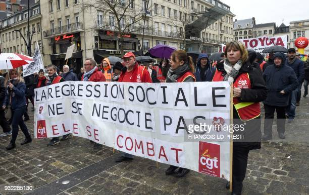 People march behind a banner reading 'We don't negociate the social regression we're fighting it' on March 15 2018 in the French northern city of...