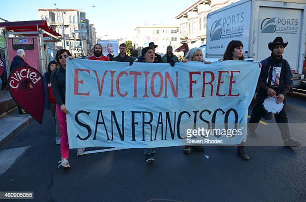 People march behind an Eviction Free San Francisco banner on 24th St after blocking an Apple bus for half an hour on Valencia St. The protest called...