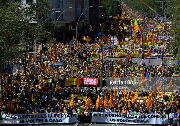 People march behind banners and wave Catalan proindependence 'estelada' flags during a demonstration to support Catalan proindependence jailed...
