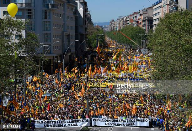 People march behind two banners reading in Catalan In favour of rights and freedoms We want you at home during a demonstration to support Catalan...