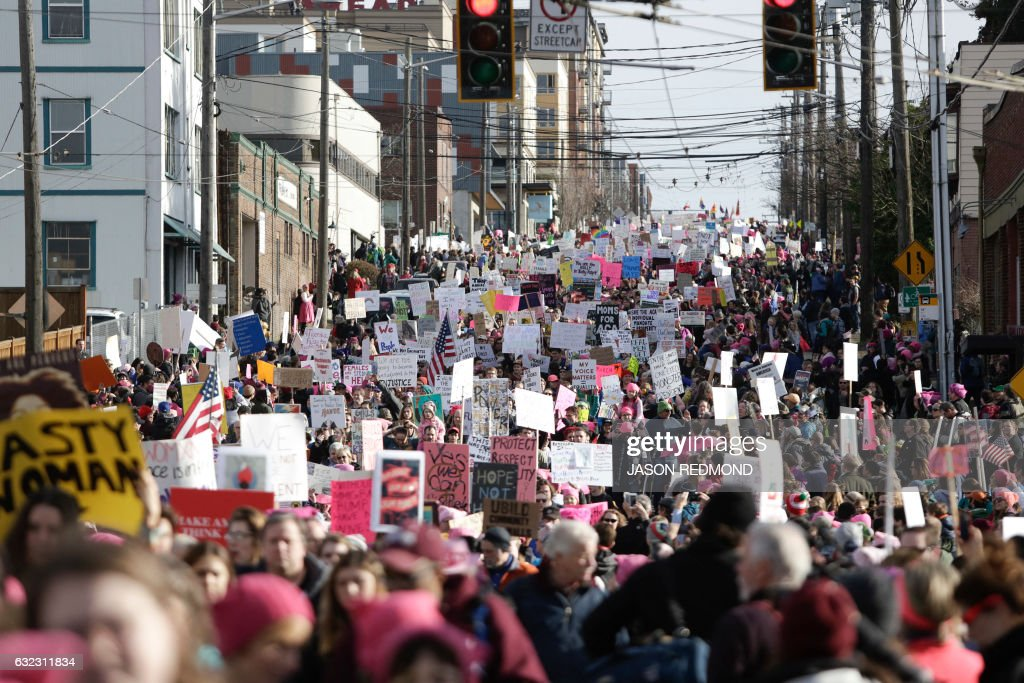 People march down South Jackson Street during the Women's March in Seattle, Washington on January 21, 2017. Led by women in pink 'pussyhats,' hundreds of thousands of people packed the streets of Washington and other cities Saturday in a massive outpouring of defiant opposition to America's hardline new president, Donald Trump. / AFP / Jason Redmond