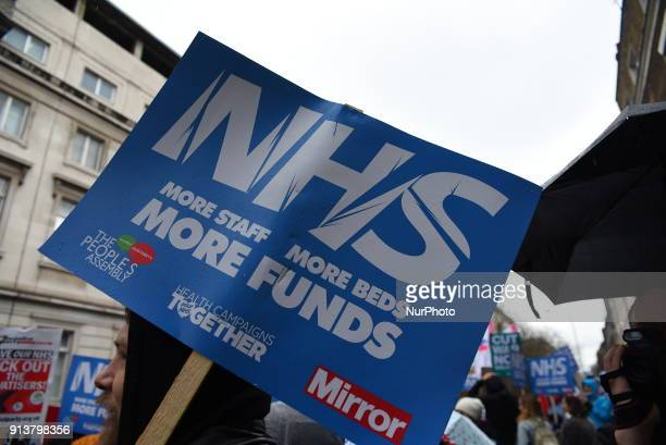 People march holding placards and standards to protest sgainst the crisis of the staterun NHS the National Health Service in central London on...