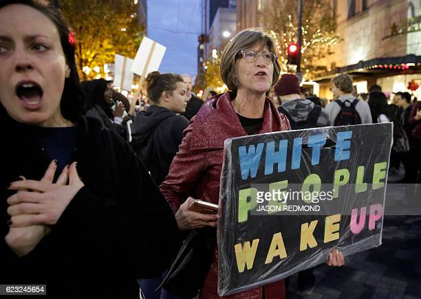 People march in protest against US Presidentelect Donald Trump in Seattle Washington on November 14 2016 Protesters have denounced Trump's...