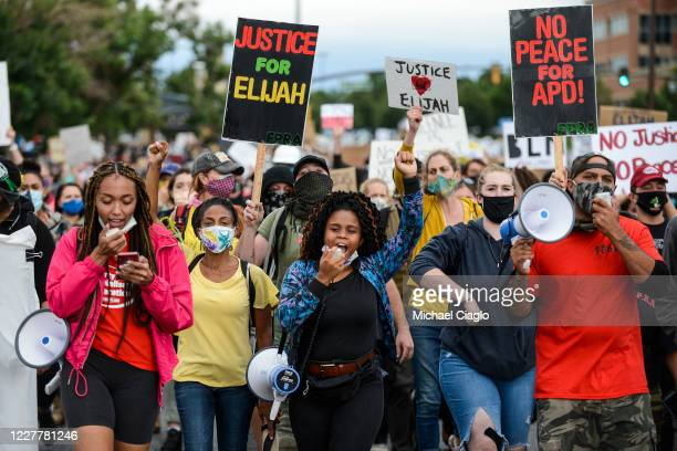 People march in the street to protest the death of Elijah McClain on July 25 2020 in Aurora Colorado On August 24 2019 McClain was walking home when...